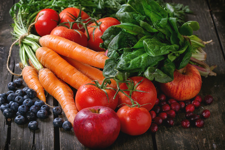 haulm: Assortment of fresh fruits, vegetables and berries carrot, spinach, tomatoes, red apples, blueberries and cranberries over old wooden table. Stock Photo