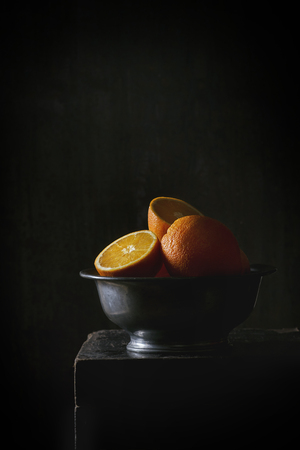 Whole and sliced oranges in vintage metal bowl over black table in the dark. Dark rustic style. With copy space at top Zdjęcie Seryjne