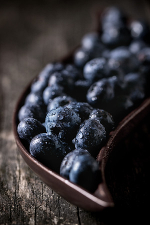 flexure: Close up of fresh wet blueberries in decorative ceramic plate over old wooden table
