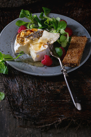 blue spotted: Blue spotted plate with grilled goat cheese served with liquid honey, lavender, raspberries, wholegrain toast and green salad. With vintage fork over old wooden table. Dark rustic style.