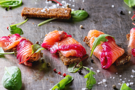 salt and pepper: Sliced salmon filet, salted with beetroot juice, served on whole wheat toasts with salad leaves, sea salt and pepper over metal surface. Top view Stock Photo