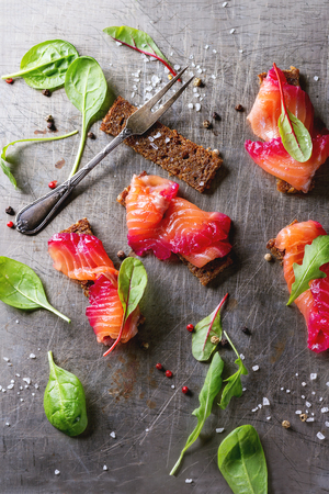 salmon filet: Sliced salmon filet, salted with beetroot juice, served on whole wheat toasts with salad leaves, sea salt and pepper and vintage fork over metal surface. Top view Stock Photo