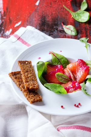 salmon filet: White ceramic plate with Sliced salmon filet, salted with beetroot juice, served with whole wheat toasts, salad leaves and beetroot sauce over red wooden surface with white textile.