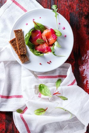 salmon filet: White ceramic plate with Sliced salmon filet, salted with beetroot juice, served with whole wheat toasts, salad leaves and beetroot sauce over red wooden surface with white textile. Top view