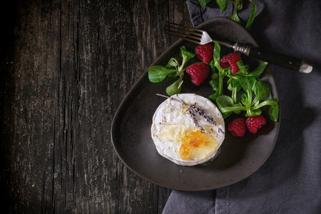 Brown ceramic plate with fresh goat cheese, served with honey, honeycomb, lavender, raspberries and green salad on gray textile napkin over old wooden table. Dark rustic style. Top view Stock fotó