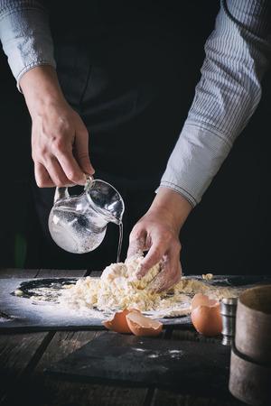 Flüssiges Wasser der weiblichen Hände vom Krug, kneten den Teig für Teigwaren auf altem hölzernem Küchentisch. Broken Eier im Vordergrund. Dunkle rustikale Art. Siehe Prozessserie