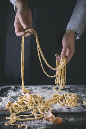 frescura: Manos femeninas que hacen la pasta pici sobre la mesa de cocina de madera, el espolvoreado de harina. estilo rústico oscuro con efecto de filtro retro. Ver la serie proceso