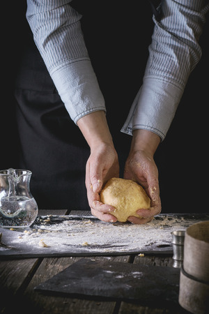 flour: Female hands hold ready-made dough for pasta on old wooden kitchen table, powdered by flour. Dark rustic style. See process series