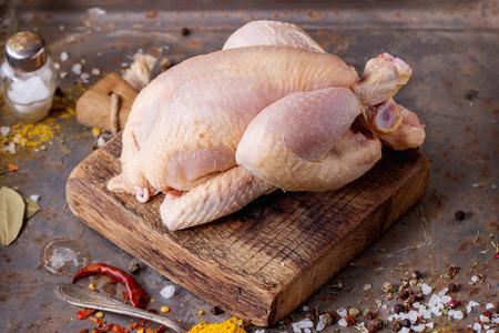 Mini pollo crudo en la tabla de cortar de madera con sal de mar y diferentes especias sobre superficie de metal viejo