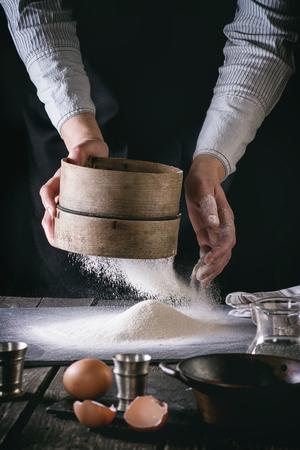 Vrouwelijke handen zeven meel uit oude zeef op oude houten keukentafel. Vintage keukengerei met bloem, water en eieren op de voorgrond. Donkere rustieke stijl met rertro filter effect. Zie proces-serie Stockfoto