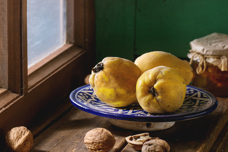 quinces: Three juicy quinces in blue ceramic plate, walnuts and jar of honey over wooden table near window with bright sunlight. With green wooden wall at background. Dark rustic style. Stock Photo