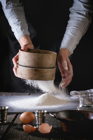 white flour: Female hands sifting flour from old sieve on old wooden kitchen table. Vintage kitchenware with flour, water and eggs at foreground. Dark rustic style. Stock Photo