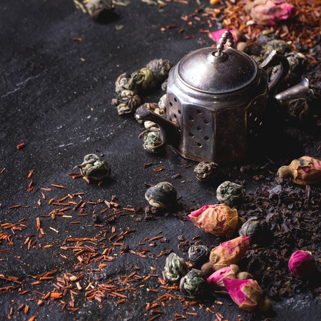 tea strainer: Assortment of dry tea with tea strainer as small teapot. Green tea, black tae, green tea with rice, rooibos, dry rose buds. Black textured slate background. Square image with selective focus