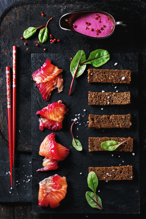 salmon filet: Sliced salmon filet, salted with beetroot juice, served with whole wheat toasts, salad leaves, beetroot sauce over black slate surface. With red chopstick at left. Top view, retro filter effect