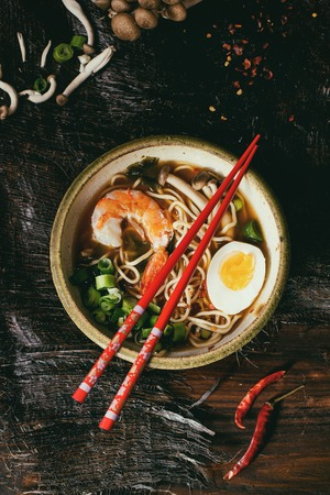 egg noodles: Ceramic bowl of asian ramen soup with shrimp, noodles, onion, sliced egg and mushrooms, served with red chopsticks and chili pepper over wooden table. Dark rustic style. Top view. Retro filter effect
