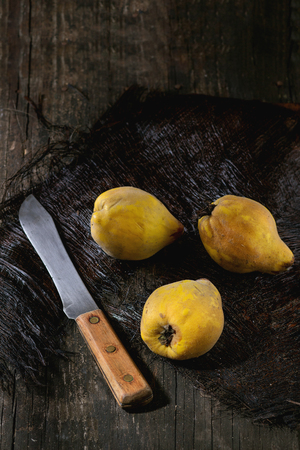 quinces: Three whole juicy quinces with vintage knife over black wooden table in sunlight. Dark rustic style.