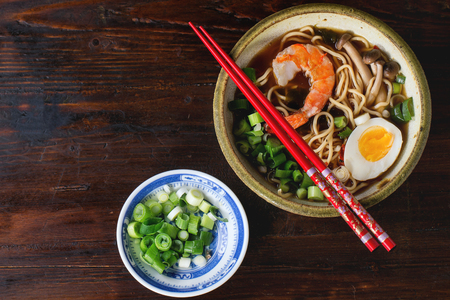 Ceramic bowl of asian ramen soup with shrimp, noodles, spring onion, sliced egg and mushrooms, served with red chopsticks and sliced spring onion over dark wooden surface. Top view