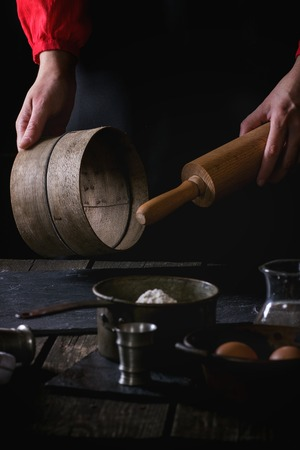 rollingpin: Female hands with wooden rolling-pin and sieve ready to cook the dough in dark rustic kitchen. Vintage kitchenware with flour, water and eggs at foreground.