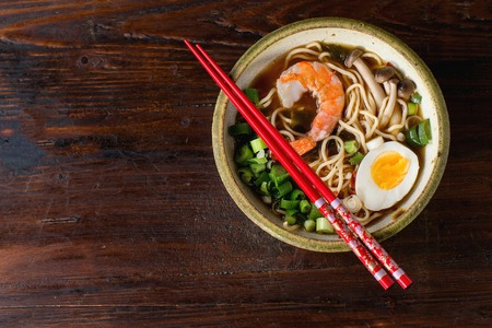 Ceramic bowl of asian ramen soup with shrimp, noodles, spring onion, sliced egg and mushrooms, served with red chopsticks over dark wooden surface. Top view