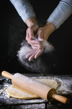 女手用粉粉末鋪開麵團與木製擀麵杖在木製廚房餐桌麵食。黑暗的鄉村風格。