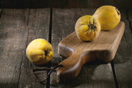 quinces: Three whole juicy quinces on old chopping board over wooden table in sunlight. Dark rustic style.