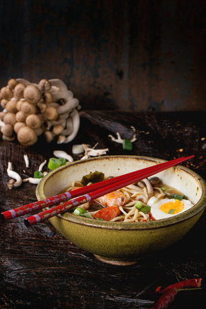 chinese meal: Ceramic bowl of asian ramen soup with shrimp, noodles, spring onion, sliced egg and mushrooms, served with red chopsticks and raw mushrooms over old wooden table. Dark rustic style.
