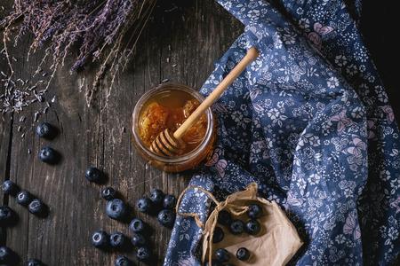 Open glazen pot vloeibare honing met honingraat en honing dipper binnen, verse bosbessen en bos van droge lavendel over oude houten tafel met blauwe textiel vod. Dark rustieke stijl. bovenaanzicht