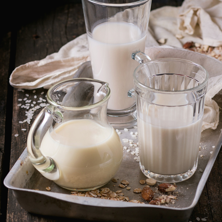 Set of non-dairy milk (rice milk, almond milk and oat milk) in glass cups and jug on old aluminum tray with rice grains, oat flakes and almond over wooden table. Dark rustic style. Square image with selective focus