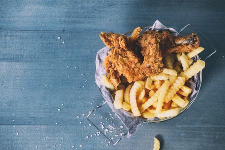 pollo frito: pollo frito tiras y las piernas con las patatas fritas en la cesta de metal sobre la mesa de madera azul con sal marina. Vista superior. Con efecto de filtro retro