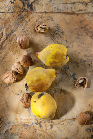 quinces: Three whole juicy quinces with whole and split walnuts over natural brown stone surface in sunlight. Top view