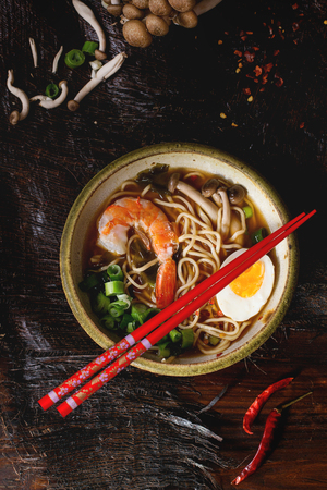 Ceramic bowl of asian ramen soup with shrimp, noodles, spring onion, sliced egg and mushrooms, served with red chopsticks and chili pepper over old wooden table. Dark rustic style. Top view