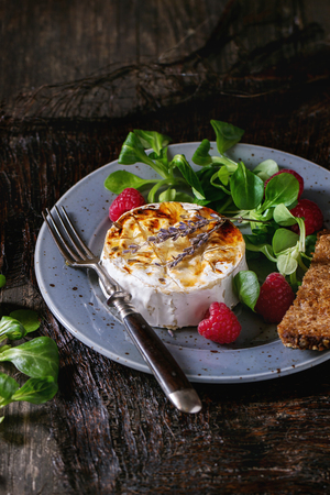 toast: Blue spotted plate with grilled goat cheese served with liquid honey, lavender, raspberries, wholegrain toast and green salad. With vintage fork over old wooden table. Dark rustic style.