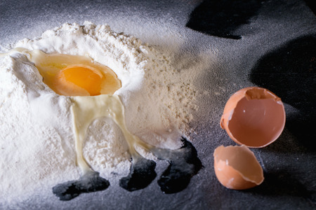brocken: Ingredients for dough making. Sifted flour and brocken egg on black slate board. Stock Photo