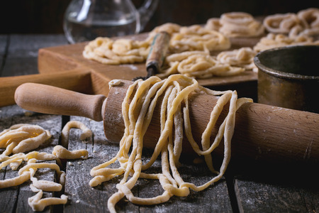 Fresh homemade pici pasta on wood chopping board over old wooden table with flour, copper bowl, rolling-pin and galss jug of water. Dark rustic style.
