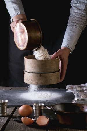 Vrouwelijke handen zeven meel uit oude zeef op oude houten keukentafel. Vintage keukengerei met bloem, water en eieren op de voorgrond. Dark rustieke stijl.