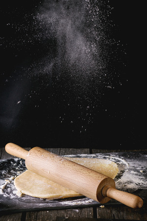 Powdering by flour rolled out dough for pasta with wooden rolling pin over wooden kitchen table. Dark rustic style.
