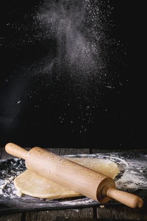 harina: Pulverización por la harina de rodar la masa para la pasta con un rodillo de madera sobre la mesa de cocina de madera. estilo rústico oscuro.