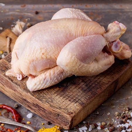 aves de corral: Mini pollo cruda en la tabla de cortar de madera con sal de mar y diferentes especias sobre superficie de metal viejo. cuadrado de imagen con enfoque selectivo Foto de archivo