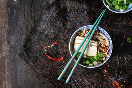 Chinese porcelain bowl of asian ramen soup with feta cheese, noodles, spring onion and mushrooms, served with turquoise chopsticks over old wooden table. Dark rustic style. Top view