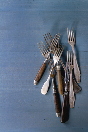 grunge flatware: Set of vintage forks over blue wooden surface. Top view Stock Photo