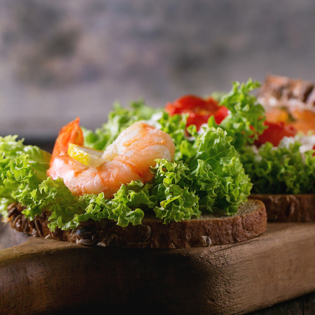 set up: Close up of sandwiches with whole wheat bread, fresh salad, feta cheese, tomatoes, shrimp and salted salmon on wooden cutting board over old wooden table. Rustic style. Square image with selective focus