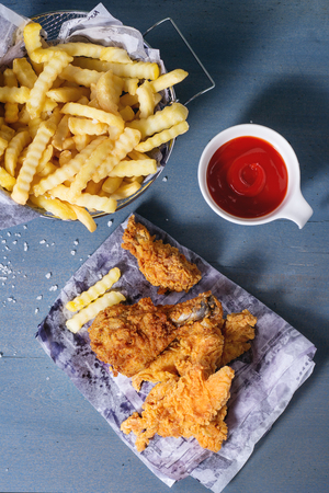 Chicken fries strips and legs on paper with basket of French fries and bowl of ketchup sauce over blue wooden table. Flat lay