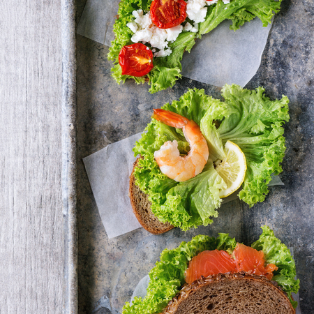 vegetable tin: Set of Sandwiches with whole wheat bread, fresh salad, feta cheese, cherry tomatoes, shrimp and salted salmon on old tin background. Top view. Square image