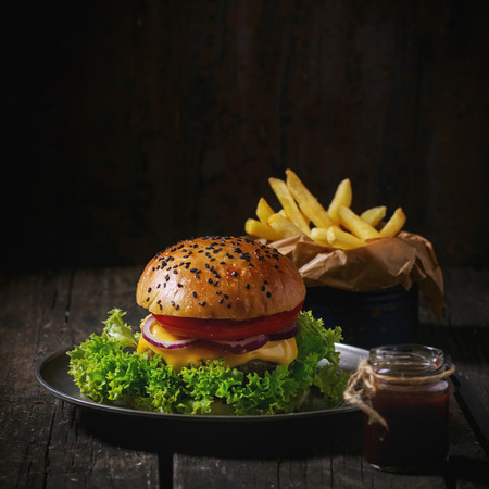 Fresh homemade hamburger with black sesame seeds in old metal plate with fried potatoes, served with ketchup sauce in glass jar over old wooden table with dark background. Dark rustic style. Square image Stock Photo