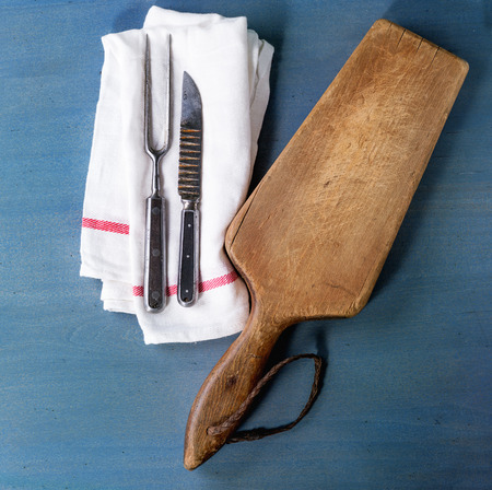 Empty wooden chopping board with vintage cutlery on white kitchen towel over blue wooden surface. Top view