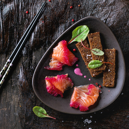 salmon filet: Triangular ceramic plate with Sliced salmon filet, salted with beetroot juice, served with whole wheat toasts, salad leaves and beetroot sauce over black surface. With black chopstick. Top view. Square image