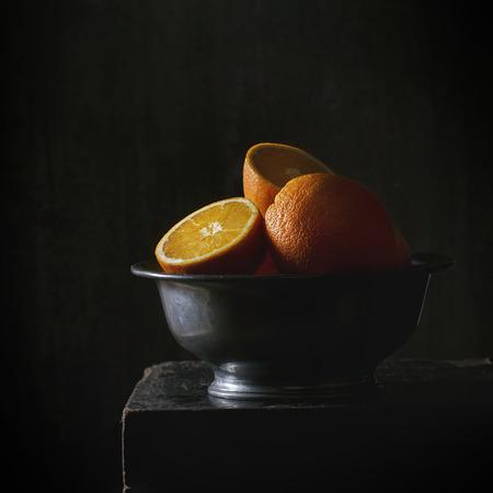 Gehele en gesneden sinaasappelen in vintage metalen kom op zwarte tafel in het donker. Dark rustieke stijl. Vierkante afbeelding met selectieve aandacht.