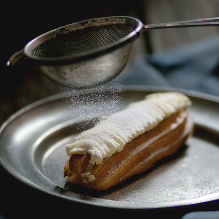 sugar powder: Single Eclair with white butter cream in vintage metal plate with Sifting sugar powder. Dark rustic style. Day light. Outside view. Square image with selective focus