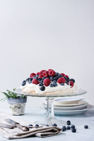 dessert stand: Vintage cake stand with Meringue dessert Pavlova with fresh blackberries and raspberries. Over blue wooden table with old tableware, textile napkin and snowdrops flowers. Stock Photo