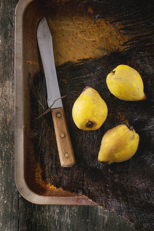 cuchillo de cocina: Three whole juicy quinces with vintage knife in rusty metal tray over black wooden table in sunlight. Dark rustic style. Top view